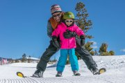 Man skiing with girl in front of him helping her learn to ski on beginner ski hill