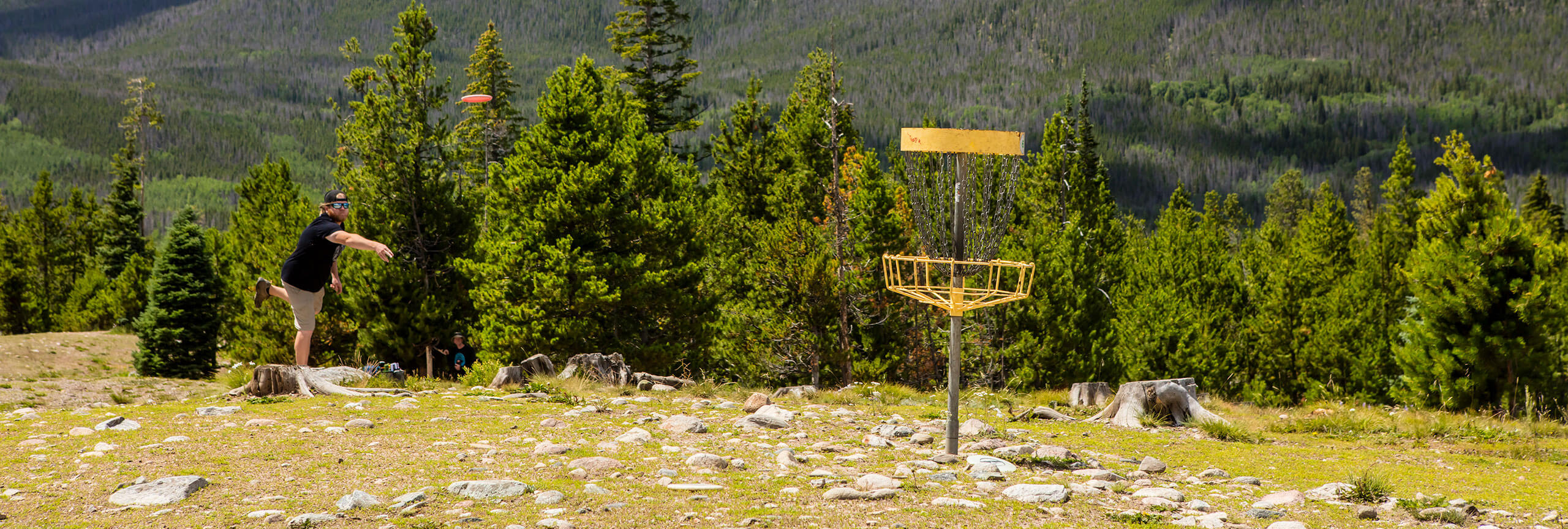 Man throwing disc at basket at disc golf course at Frisco Adventure Park