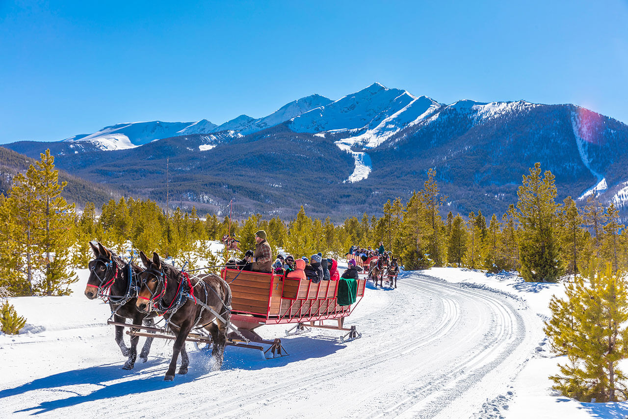 View of two groups of sleigh rides on snowy trail with mountains in background at Frisco Adventure Park