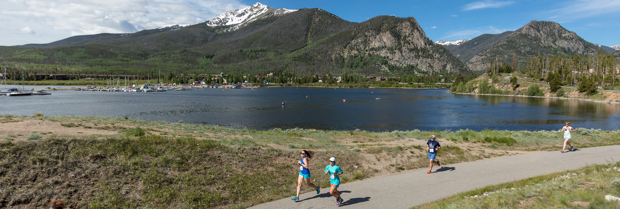 Runners running on rec path Dillon Reservoir and Ten Mile Mountains in background