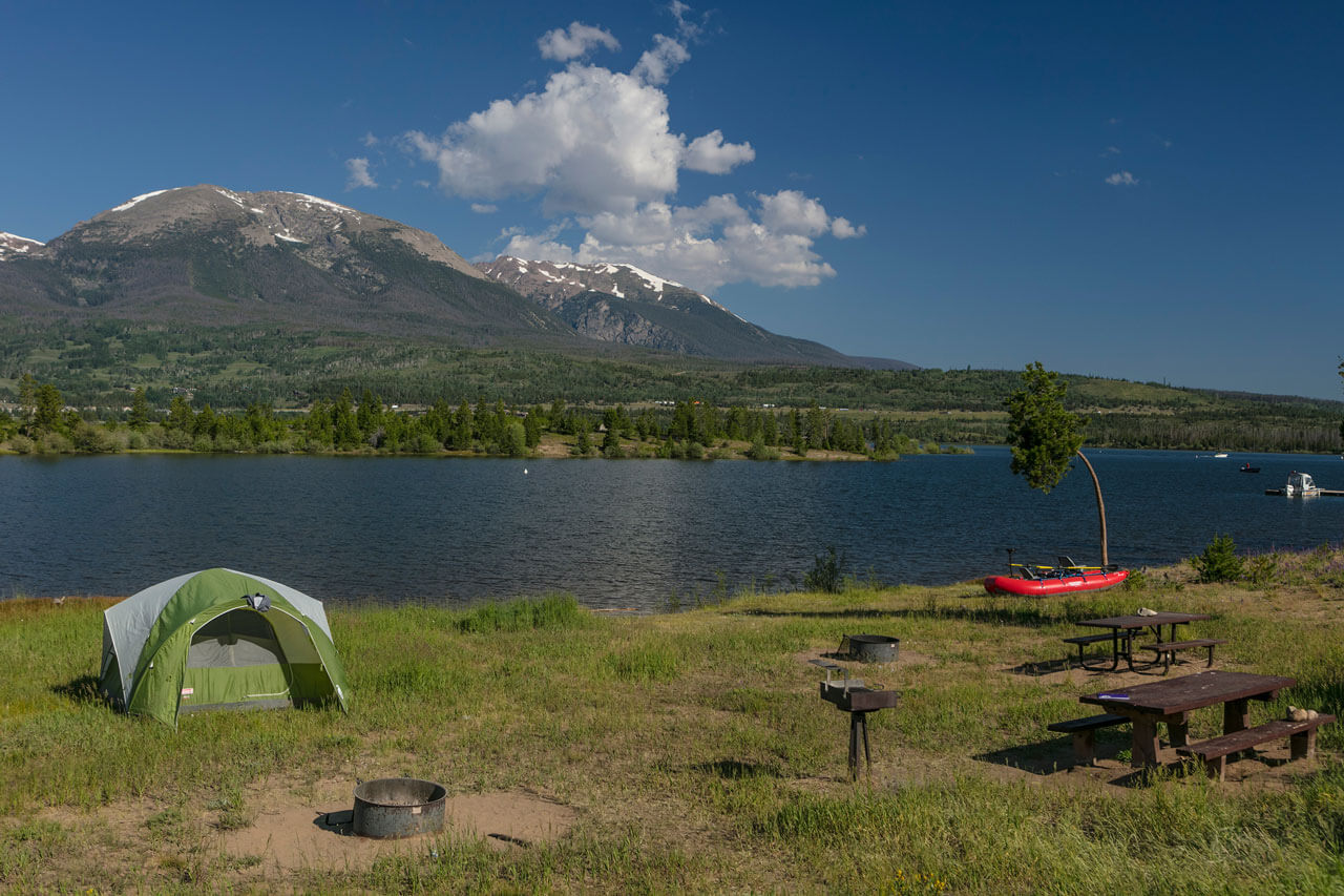 A tent set up with a boat nearby, with Lake Dillon and Buffalo Mountain in the background.