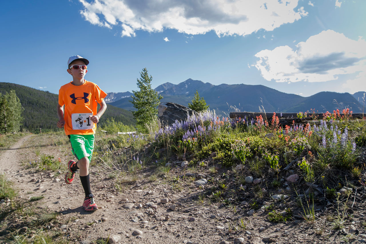 A boy in bright orange running on a trail alongside wildflowers with Tenmile Range in the background.