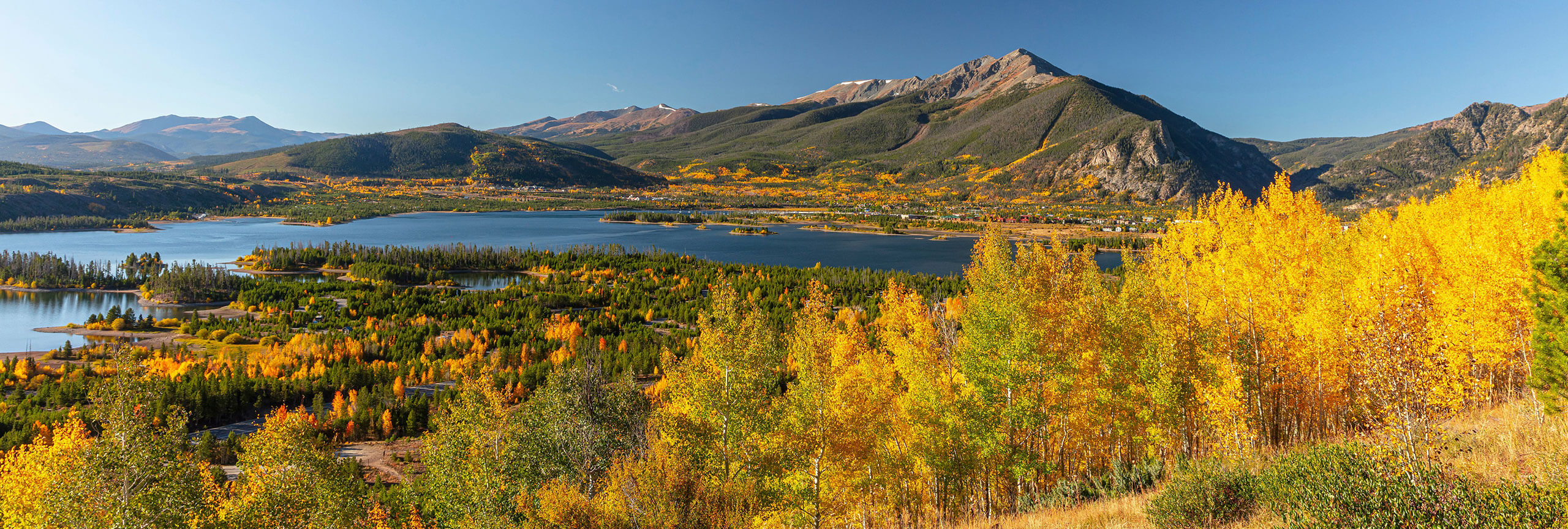 Scenic view of Lake Dillon and the Tenmile Range with yellow aspens in the foreground.