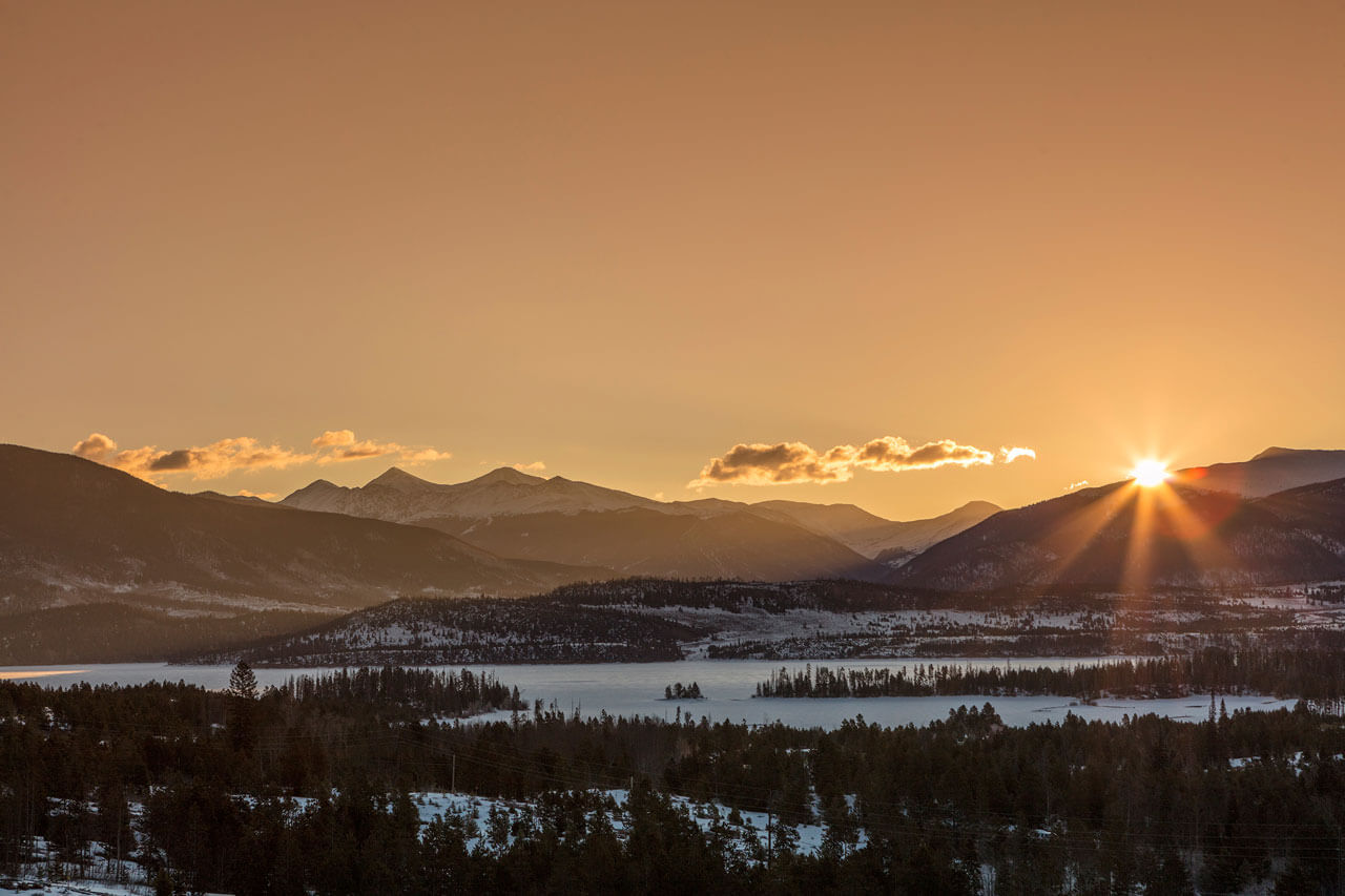 Sunset over mountains and a frozen Lake Dillon.