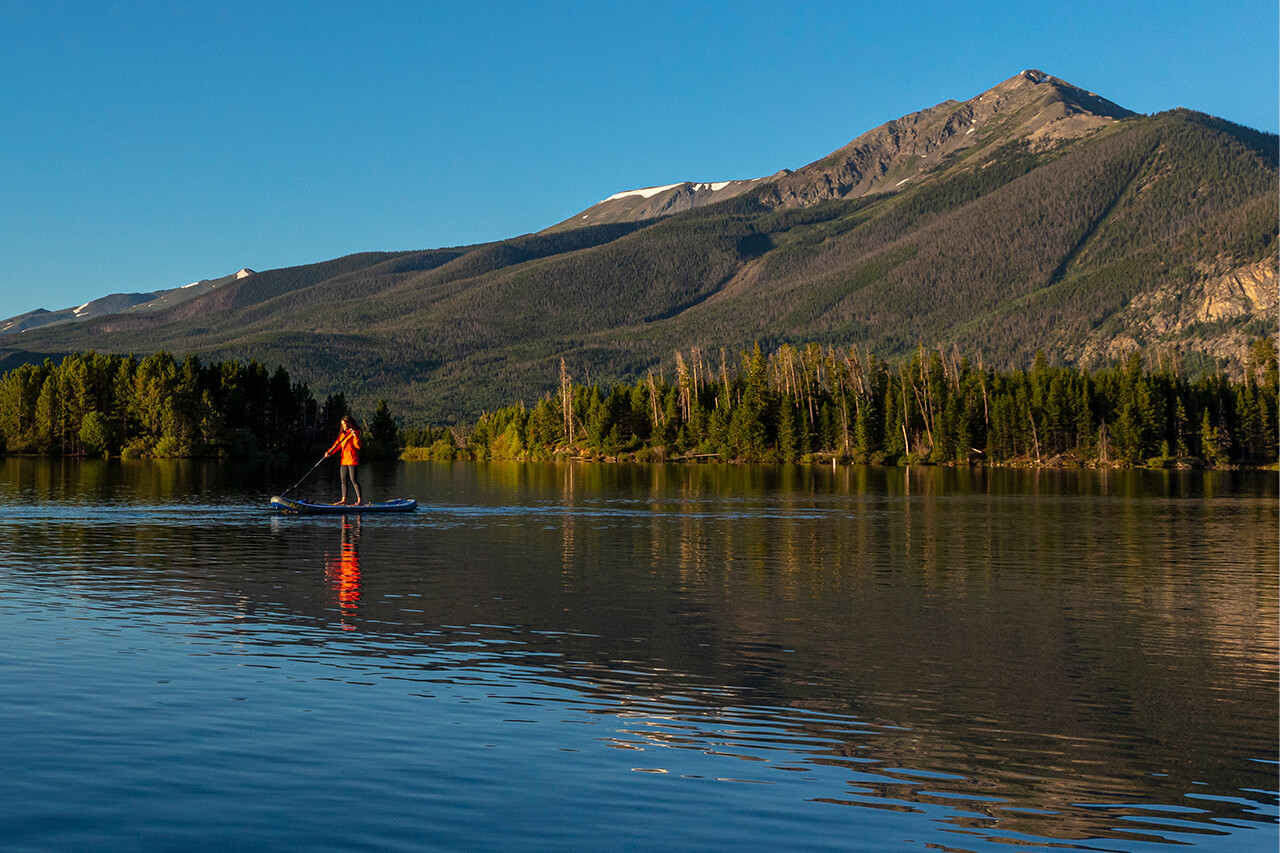 Solo standup paddle boarder on Lake Dillon, Peak One in the background.