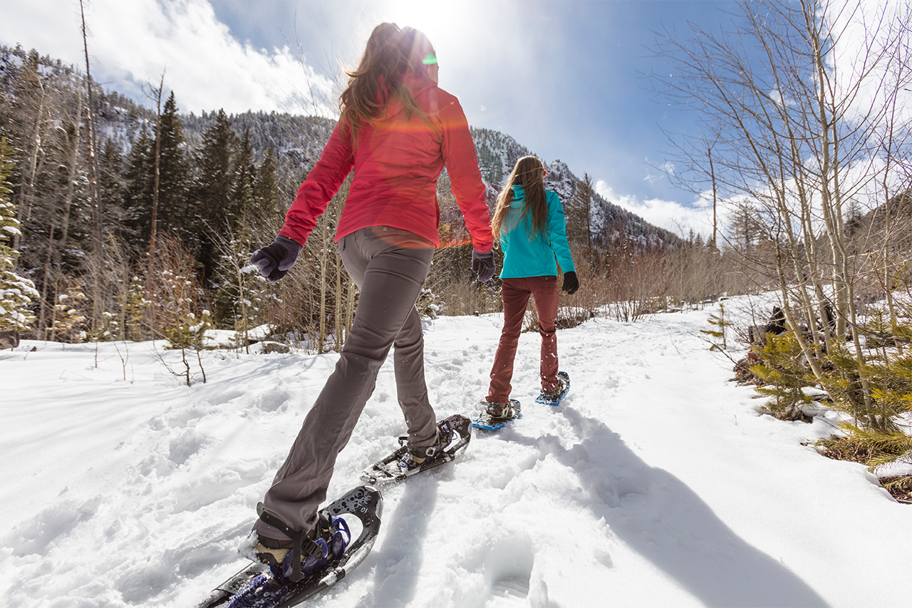 Two women snowshoeing in a trail on a sunny winter day.