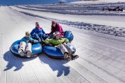 Family of four in tubes on the tubing hill at the Frisco Adventure Park