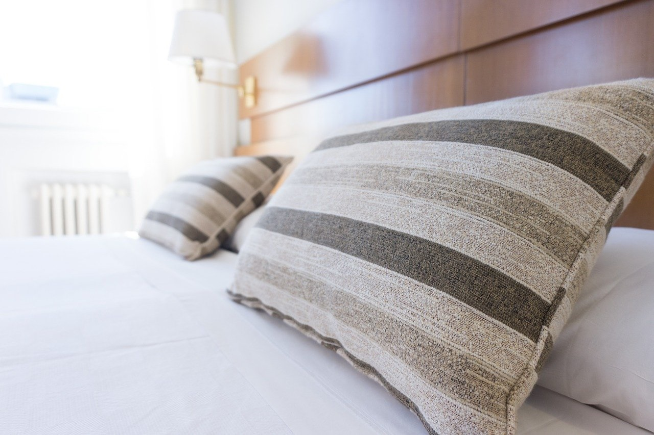 Closeup of striped pillows on white bed.