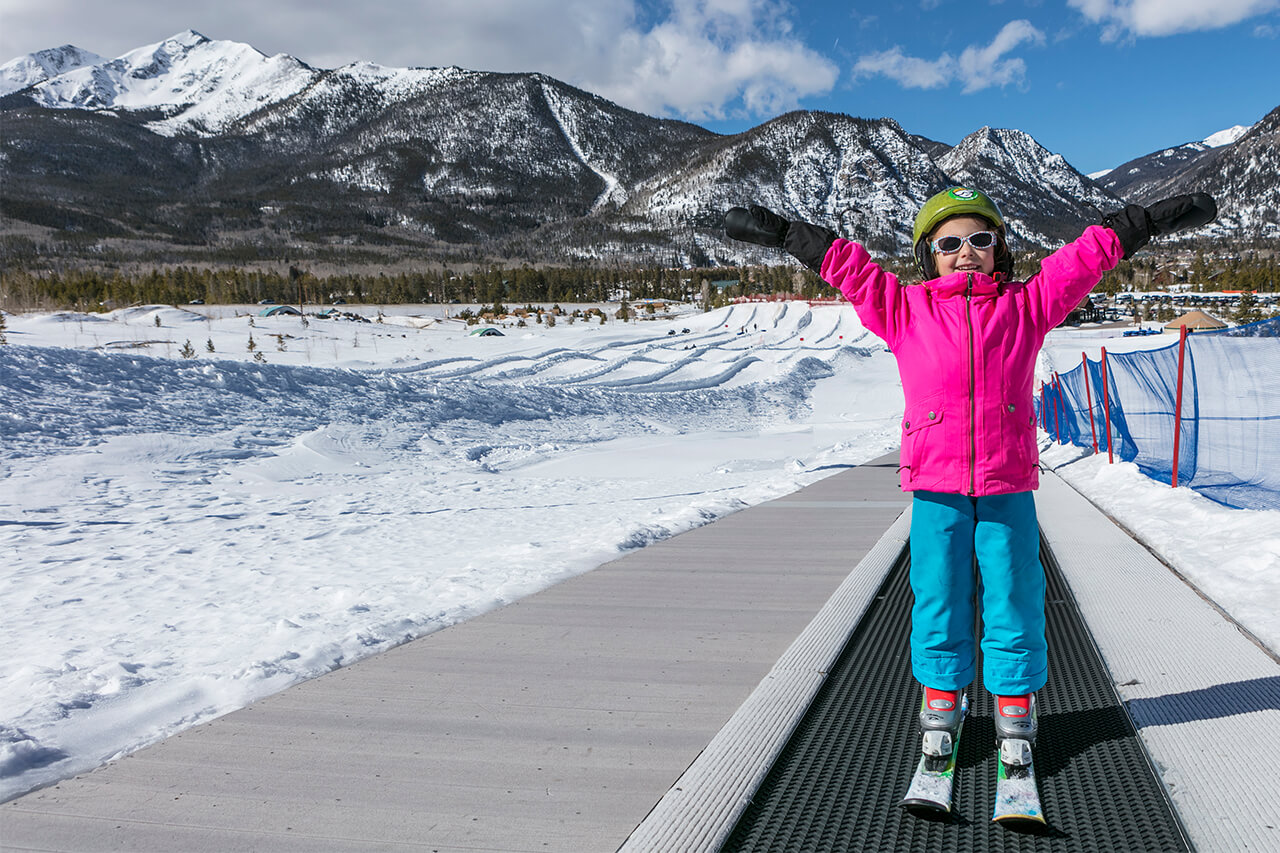 Girl on skis holding hands up and standing on surface lift at Frisco Adventure Park