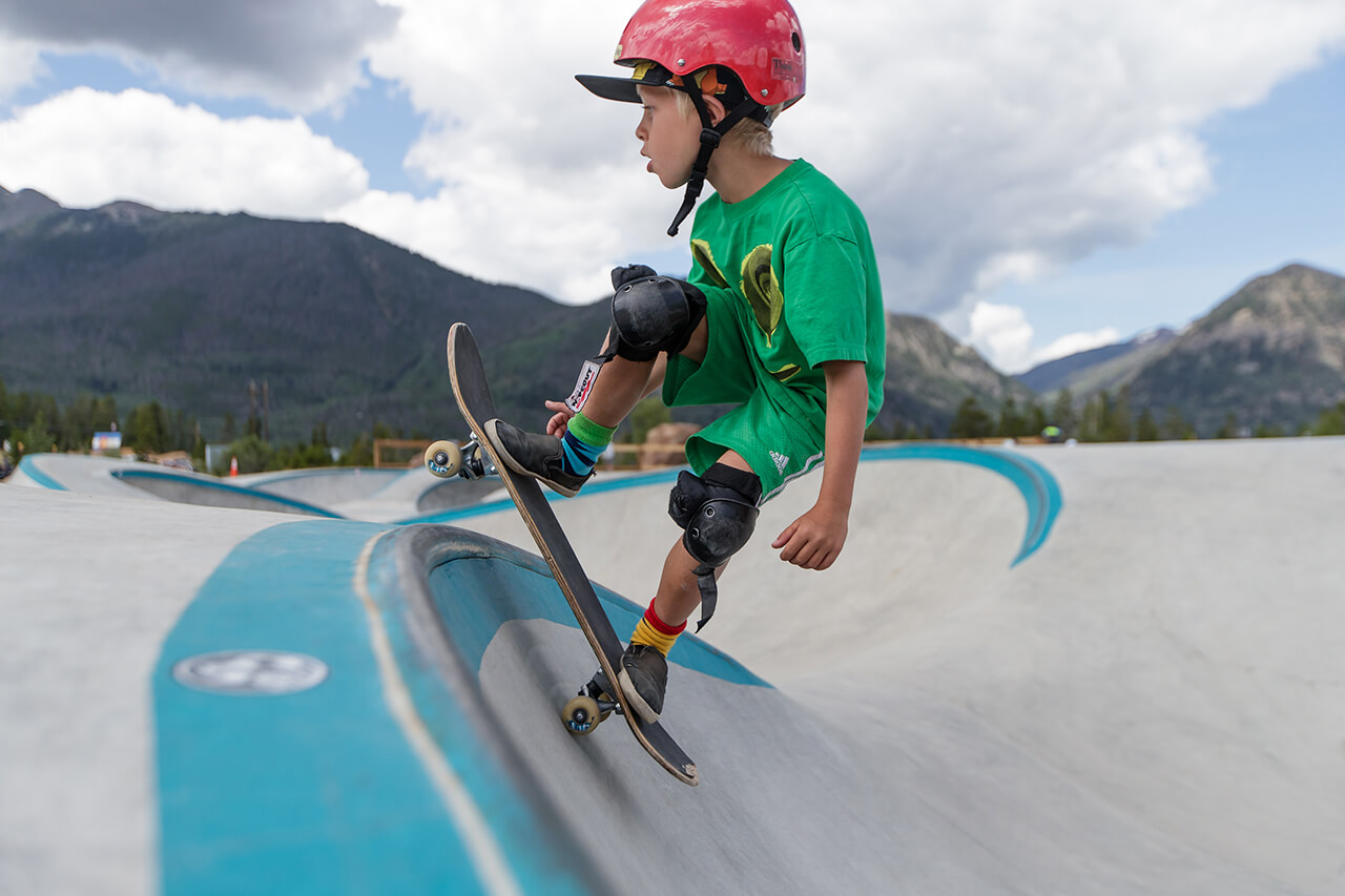 Boy wearing green with red helmet skating in Frisco Skate Park