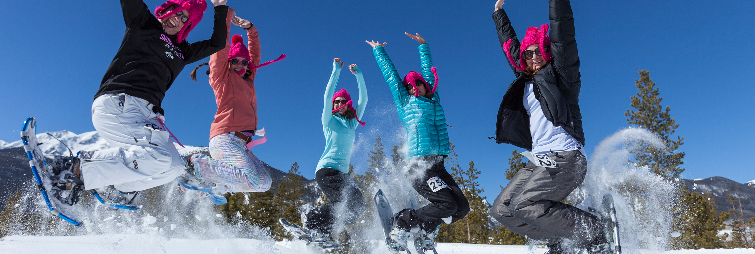 Group of women wearing snowshoes and pinks hats jumping in the air in snow