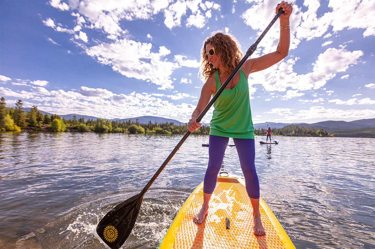 Two girls on standup paddle boards on Lake Dillon.