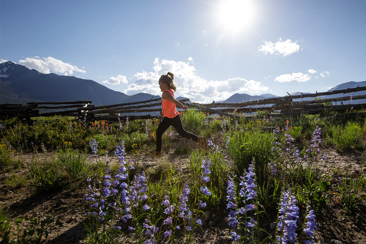 Girl running on trail at Frisco Peninsula with flowers and sun