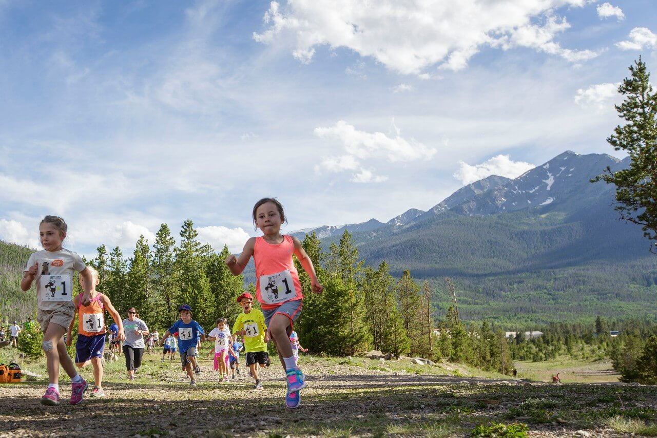 Group of kids running on dirt road at Mountain Goat Kids' Trail Running Series