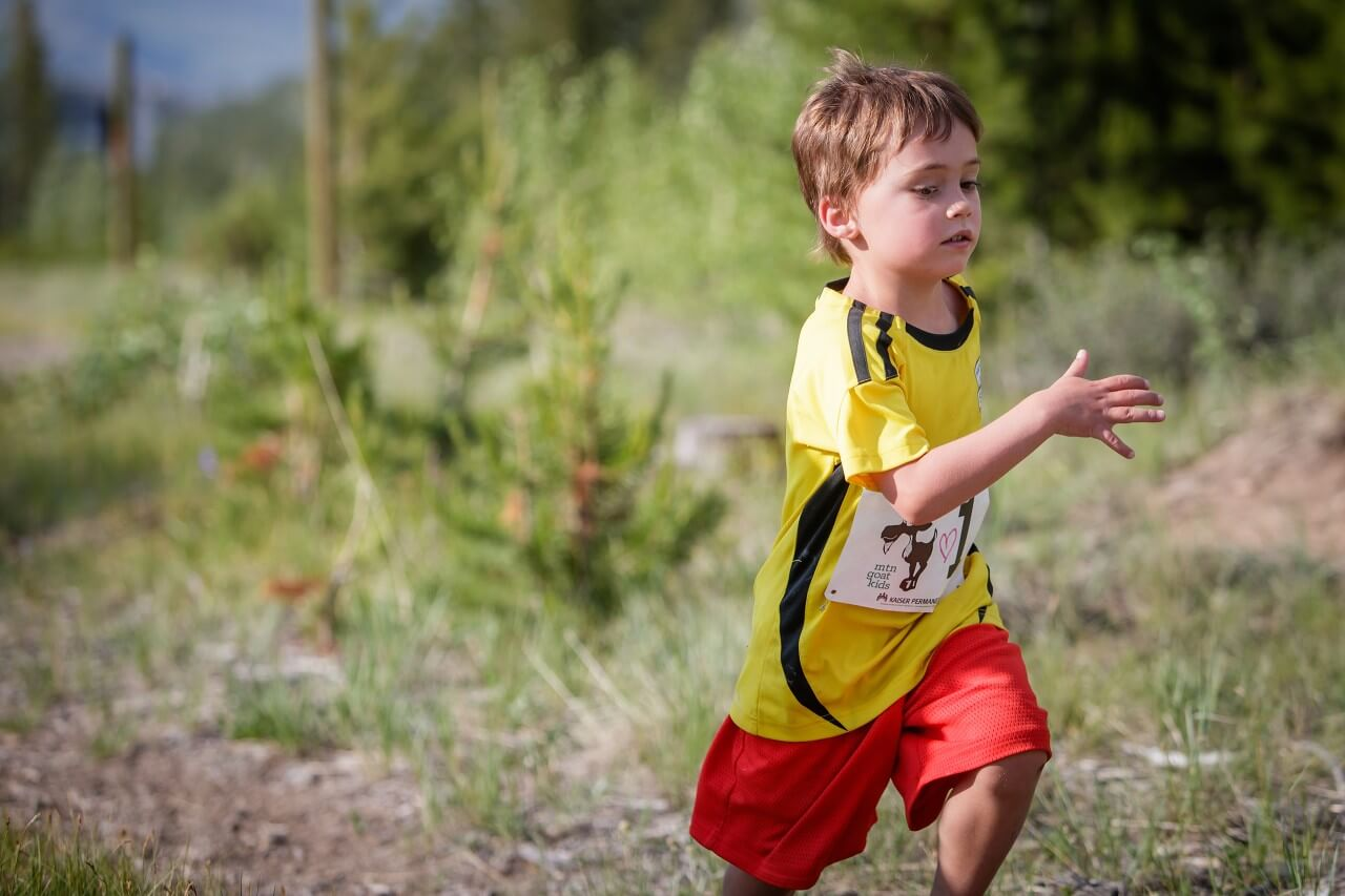 Boy in yellow shirt running on trail at Mountain Goat Kids' Trail Running Series
